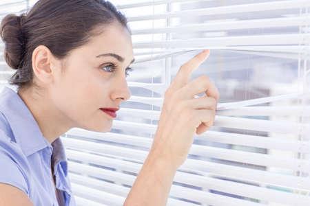 nosey: Pretty businesswoman peeking through a venetian blind in a bright office