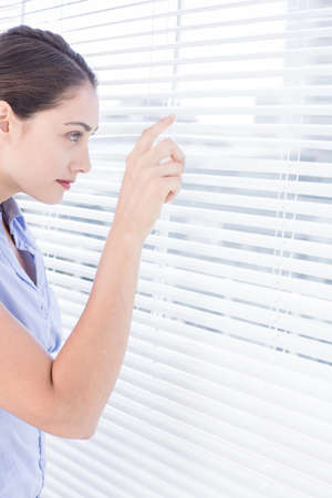 nosey: Attractive businesswoman peeking through venetian blind in a bright office
