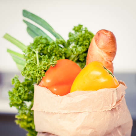 putting in: Selection of raw vegetables putting in a paper bag