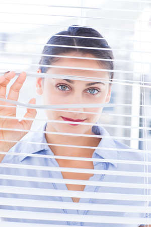 nosey: Smiling businesswoman looking through a venetian blind in an office LANG_EVOIMAGES
