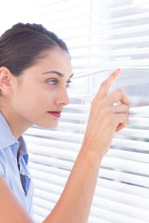 nosey: Brunette businesswoman peeking through a rollerblind in bright office