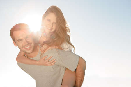 light hair: Happy man giving a piggy back to his girlfriend on a sunny day