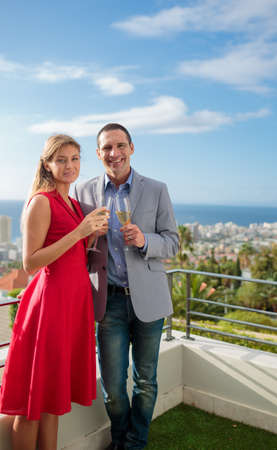 lovely couple: Lovely couple toasting with champagne on the balcony LANG_EVOIMAGES