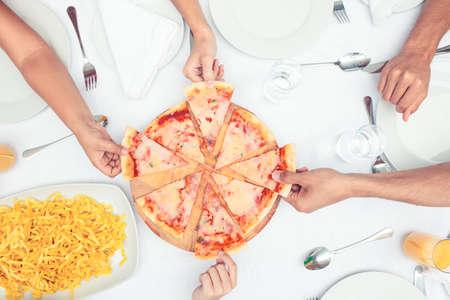 Hände Wahl Stück Pizza für eine Tabelle LANG_EVOIMAGES