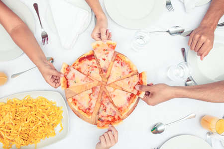 unwholesome: Hands choosing slice of pizza against a table