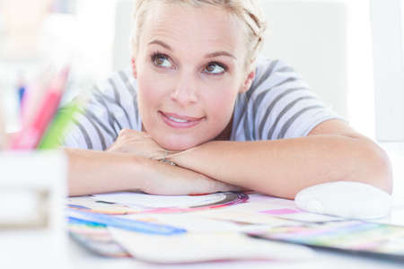 colour wheel: Cheerful designer posing on her desk in front of a colour wheel
