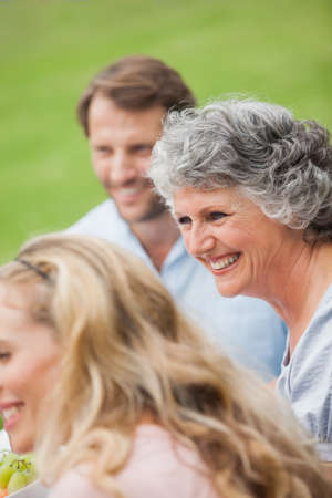 adult offspring: Smiling retired woman with her family outside on a summers day