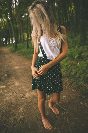 off path: Gorgeous blonde standing on forest track in the woods LANG_EVOIMAGES