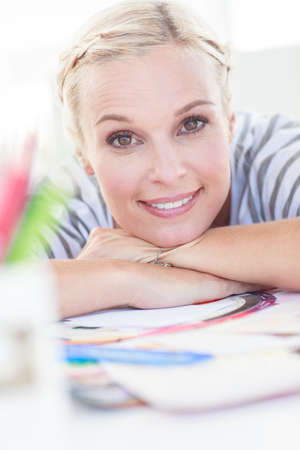 colour wheel: Pretty designer posing on her desk in front of a colour wheel