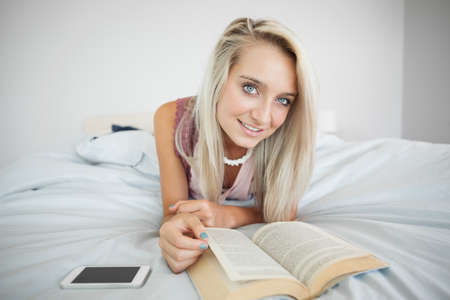 gleeful: Gorgeous gleeful blonde reading a book in bright bedroom