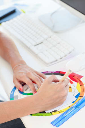 colour wheel: Designer working with a colour wheel on her desk LANG_EVOIMAGES