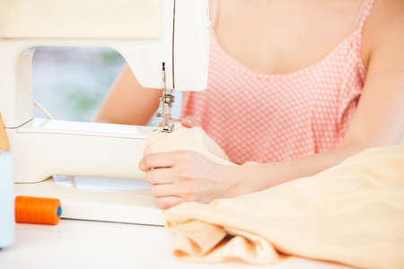 at her desk: Fashion designer using a sewing machine sat at her desk LANG_EVOIMAGES