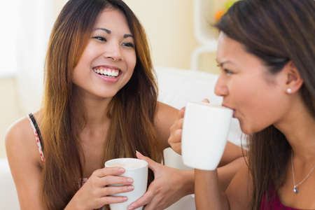 hot asian: Two pretty brunette sisters drinking a coffee while sitting on a couch