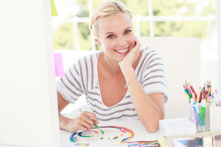 colour wheel: Happy designer working with a colour wheel in a modern office