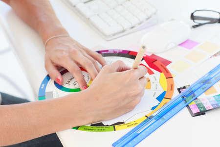 colour wheel: Designer working on a colour wheel on her desk