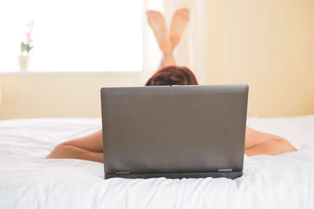 covering face: Woman using laptop lying on bed at home with laptop covering face LANG_EVOIMAGES