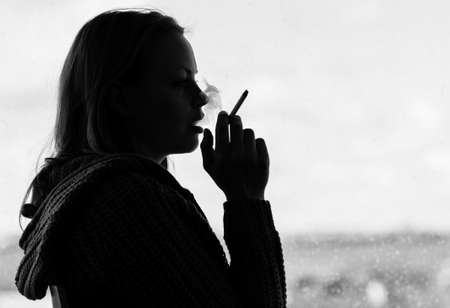 lonesomeness: Silhouette of woman smoking cigarette in black and white
