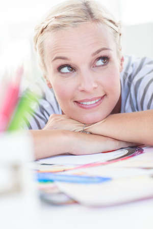 colour wheel: Happy designer posing on her desk in front of a colour wheel