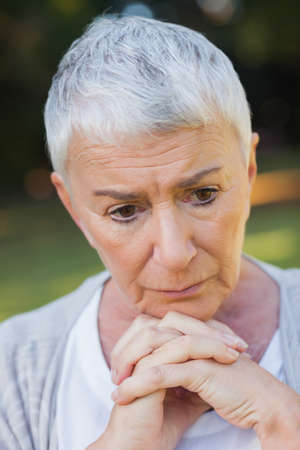 short haired: Pensive short haired elderly woman posing in a park LANG_EVOIMAGES