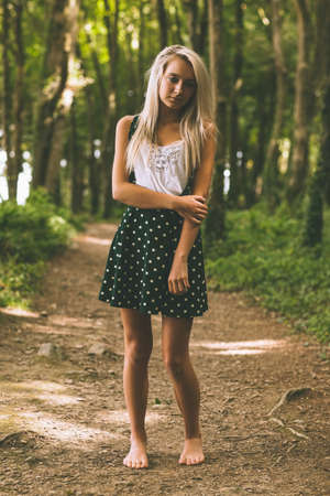 off path: Serious gorgeous blonde standing on forest track in the woods