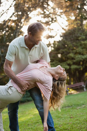 light hair: Man bending his wife while dancing in the backyard outside on a summers day