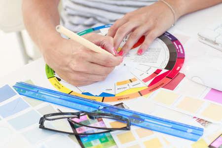 colour wheel: Female designer working on a colour wheel on her desk