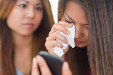 comforted: Crying woman looking at phone being comforted by her sister at home in living room