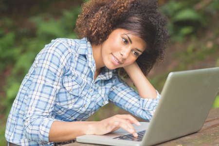 technology: Gorgeous happy brunette sitting at picnic table with laptop in nature LANG_EVOIMAGES