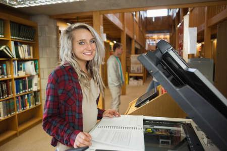 fotocopiadora: Estudiante rubia alegre de pie junto a la fotocopiadora de la biblioteca en un colegio