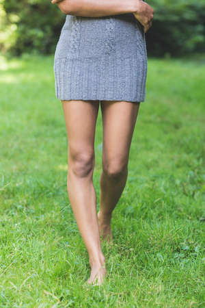 lower body: Lower body of attractive model walking on grass in nature