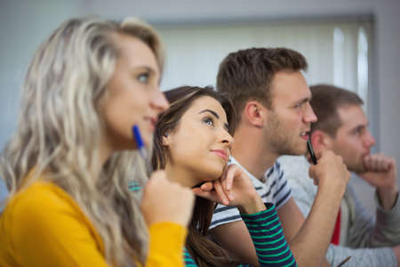 day dreaming: Day dreaming brunette student between classmates in classroom in a college