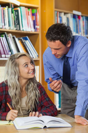 lecturer: Lecturer explaining something to blonde smiling student in library in a college