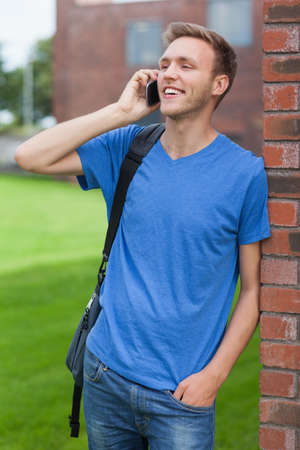 phoning: Cheerful handsome student leaning against wall phoning on college campus