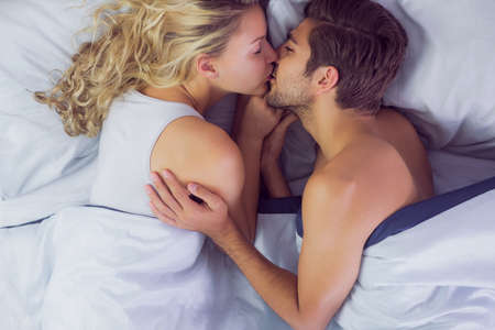 light hair: Cute young couple kissing each other while lying in their bed