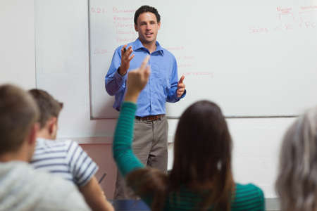 lecturer: Student raising her arm and lecturer gesturing in classroom in a college