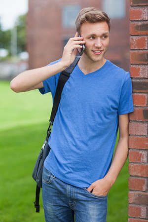 phoning: Happy handsome student leaning against wall phoning on college campus