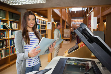 photocopier: Smiling brunette student standing next to photocopier in library in a college
