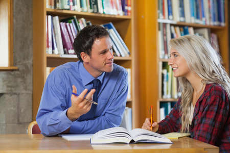lecturer: Lecturer explaining something to smiling blonde student in library in a college