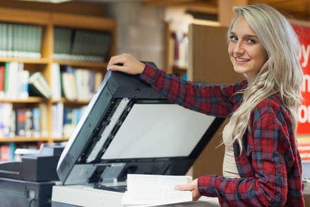 fotocopiadora: Estudiante bastante rubia usando una fotocopiadora en la biblioteca en un colegio