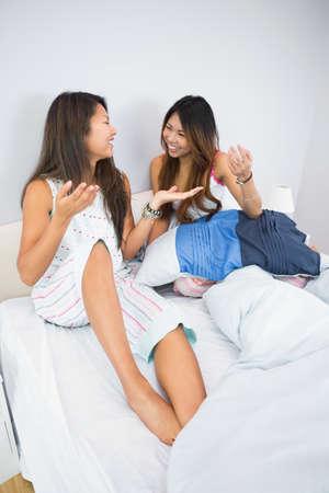 pijamada: Dos hermanas muy sentado en una cama en un dormitorio