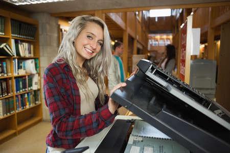 fotocopiadora: estudiante rubia alegre que usa la fotocopiadora en la biblioteca en una universidad