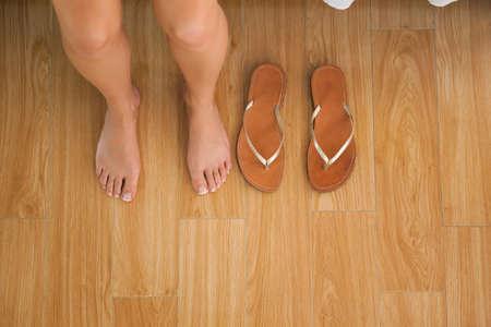 flops: Woman sitting on edge of bed beside her flip flops at home in bedroom LANG_EVOIMAGES
