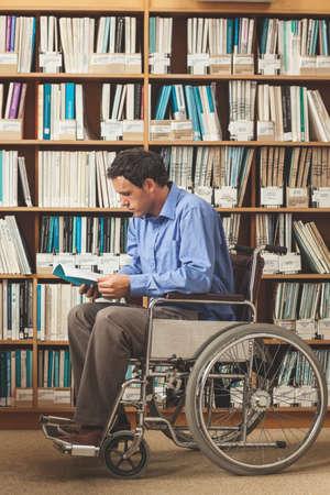 persona leyendo: Enfocado hombre sentado en silla de ruedas leyendo un libro en la biblioteca en una universidad