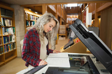 fotocopiadora: Focused blonde student standing next to photocopier in library in a college