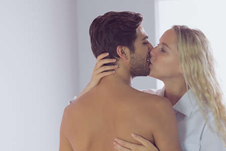 kiss love: Attractive young couple standing in the bedroom and kissing each other