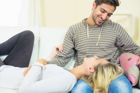 snuggling: Lovely young woman snuggling with her boyfriend in the living room LANG_EVOIMAGES