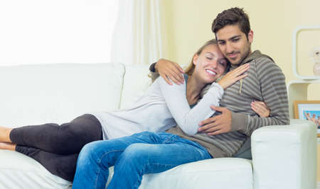 couple on couch: Cute couple sitting on couch cuddling