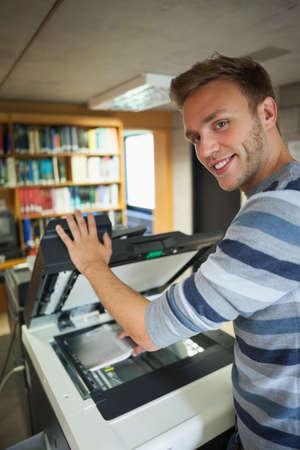 fotocopiadora: Sonriendo apuesto estudiante usando una fotocopiadora en la biblioteca en un colegio
