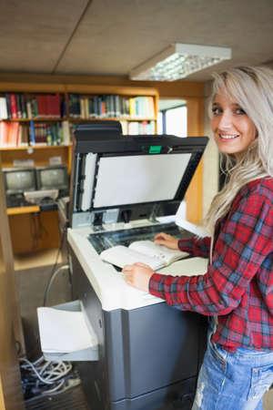 fotocopiadora: Sonriendo estudiante rubia usando una fotocopiadora en la biblioteca en una universidad