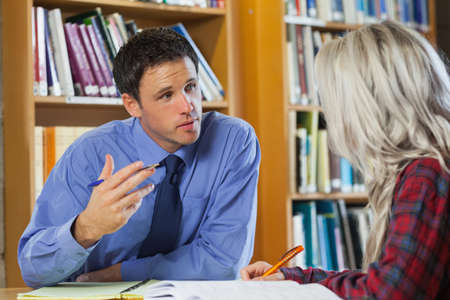 lecturer: Lecturer explaining something to blonde student in library in a college